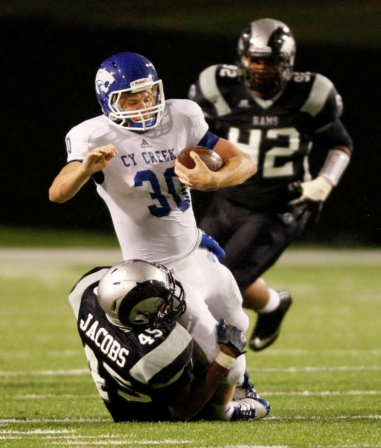 Cy-Creek quarterback Luke Allen (30) is brought down by Cy-Ridge's Anthony Jacobs during the first half of a high school football game, Friday, October 18, 2013 at Pridgeon Stadium in Houston. Photo: Eric Christian Smith, For The Chronicle