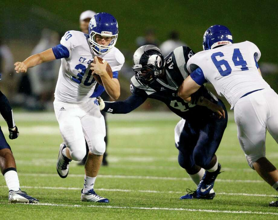 Cy-Creek quarterback Luke Allen (30) scampers past Cy-Ridge's Jordan Molden (48) during the first half of a high school football game, Friday, October 18, 2013 at Pridgeon Stadium in Houston. Photo: Eric Christian Smith, For The Chronicle