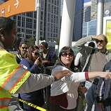 With the BART transit system on strike, AC Transit supervisor Ken Harris, left, directs people to the right bus stop at the Transbay Terminal Friday, Oct. 18, 2013, in San Francisco. Commuters in the San Francisco Bay Area got up before dawn on Friday and endured heavy traffic on roadways, as workers for the region's largest transit system walked off the job for the second time in four months. About 400,000 riders take BART every weekday on the nation's fifth-largest commuter rail system. (AP Photo/Eric Risberg)