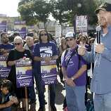 Chris Finn, right, a 17-year BART train operator and union official, speaks at a worker's rally on Friday, Oct. 18, 2013, in Oakland, Calif. Commuters in the San Francisco Bay Area got up before dawn on Friday and endured heavy traffic on roadways, as workers for the region's largest transit system walked off the job for the second time in four months.(AP Photo/Marcio Jose Sanchez)