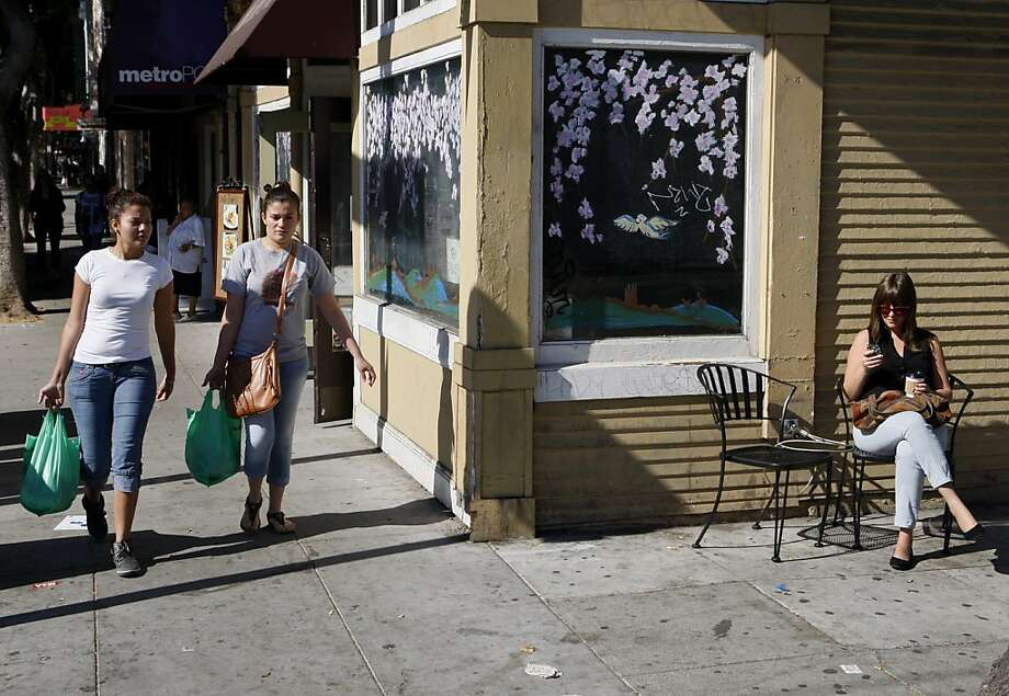 Lucy Rodriguez (left) and Yorleny Juarez stroll down 24th while Samantha Bell sits outside Bello Coffee. Photo: Raphael Kluzniok, The Chronicle