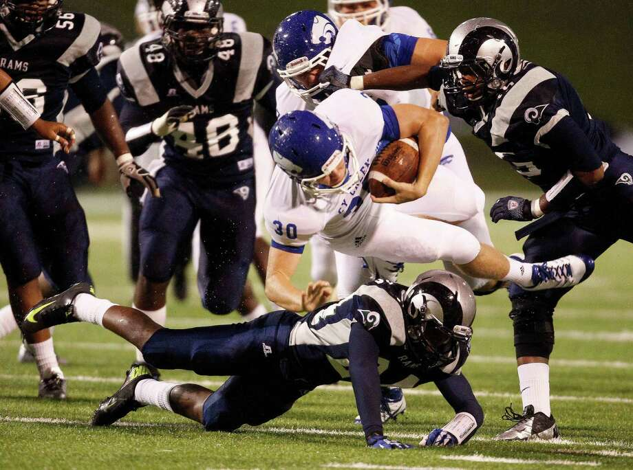 Cy Creek quarterback Luke Allen (30) is sent airborne by Cy Ridge defender Marquis Jones after taking off on a scamper during the first half of Friday night's game at Pridgeon Stadium. Photo: Eric Christian Smith, Freelance