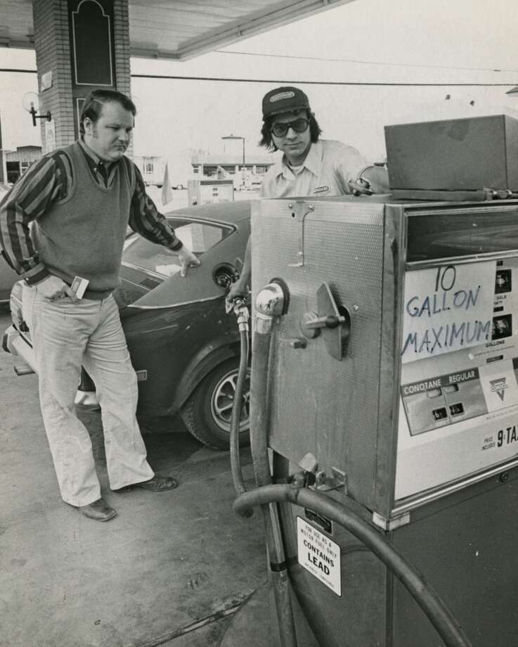 On Dec. 21, 1973, John O. Pickett (left) waits while attendant Ron West pumps gas into Pickett's car at the Westchester Conoco station on Memorial Drive at Dairy Ashford Street in Houston. The station limited  sales over the holiday weekend to 10 gallons per customer while most Texas stations closed. Photo: Orie Collins, Houston Chronicle