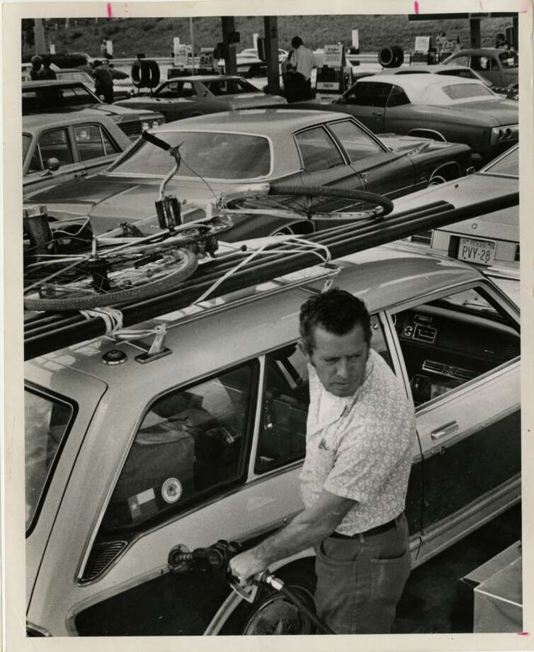 Alfred Wilson fills up his car at a crowded Exxon service station at Newcastle Drive and the Southwest Freeway in Houston in March 1974. Wilson said he drove with a bicycle on top of his car in case he ran out of gas and had to cycle to a service station. Photo: Bela Ugrin, Houston Chronicle