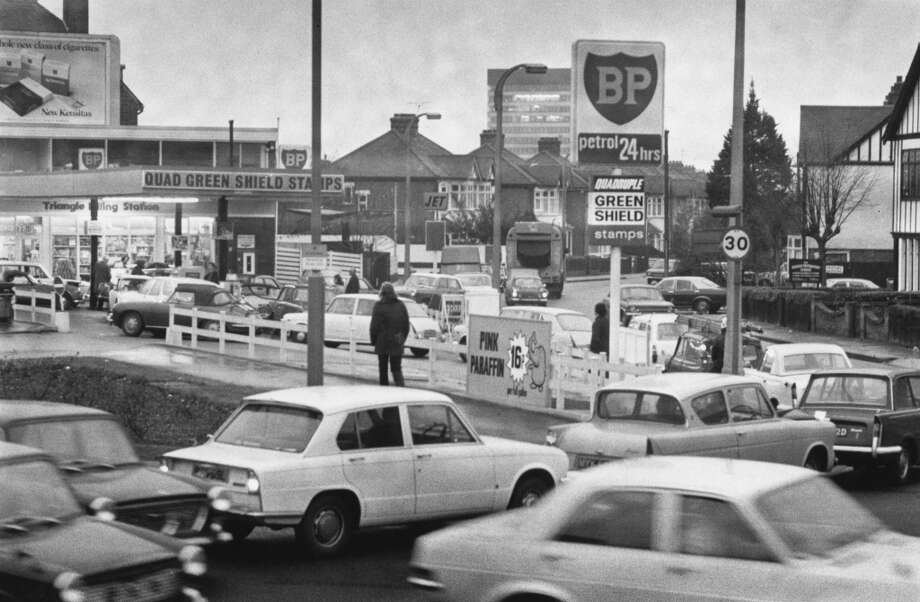 Cars line up at a petrol station on Woodford Avenue in London in December 1973 during the fuel shortage that resulted from the OPEC oil embargo. Photo: Evening Standard, Getty Images