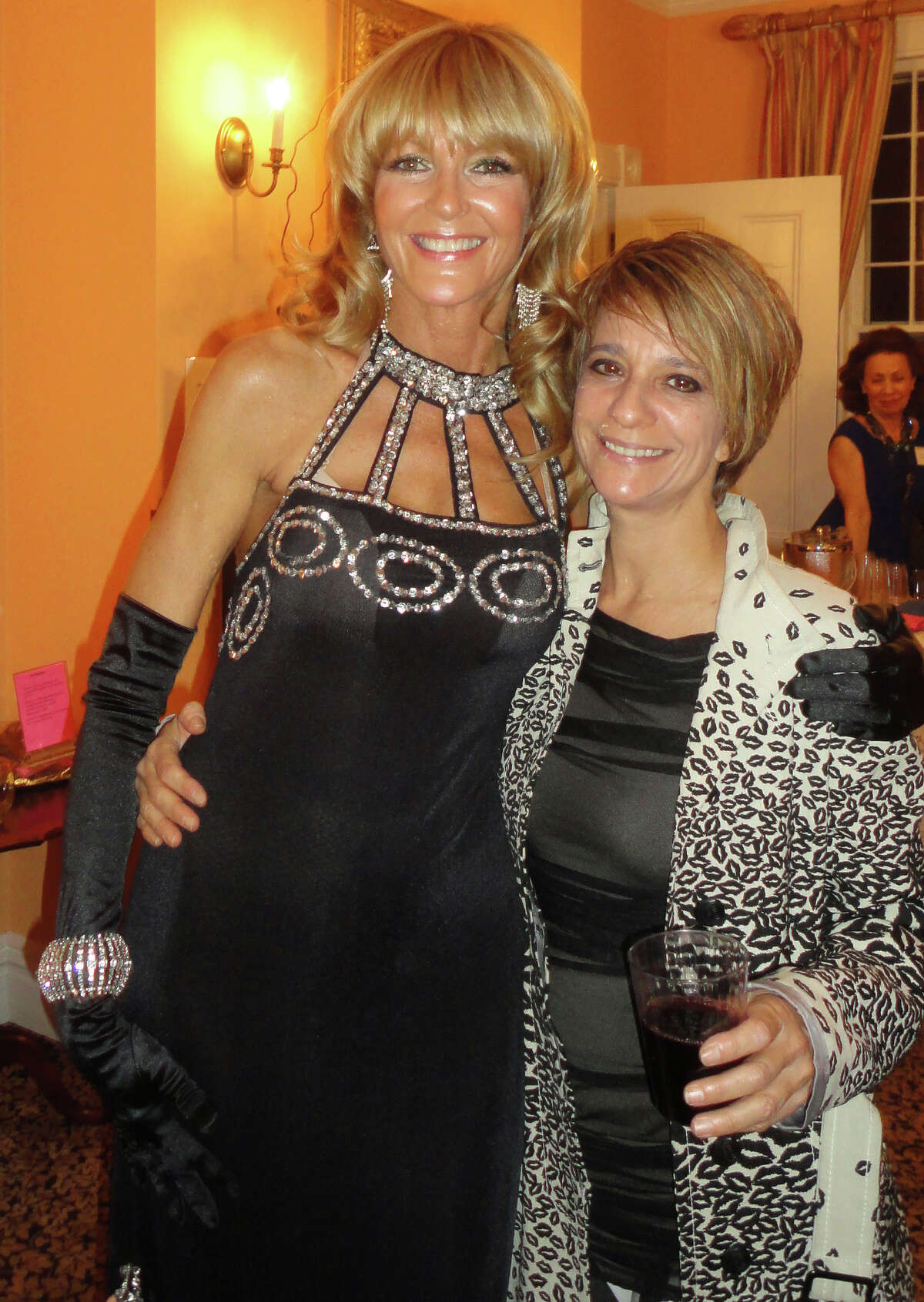Westport artist Liz Beeby wears a black vintage gown with silver sequins trim Friday as she poses at the Westport Woman's Club with Paula Gallo of Westport, a recipient of a Westport Woman's Club scholarship. Proceeds of the fashion show will go to the club's scholarship program.
