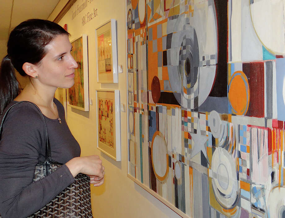 "Elinor Garcia of Fairfield examines Sarah Frassinelli's ""Circles & Stars"" at Friday's preview of the Pequot Library's 16th annual Art Show. Photo: Mike Lauterborn / Fairfield Citizen contributed"
