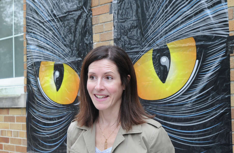 Michelle Luksic of Greenwich stands in front of a poster of a pair of owl eyes during the Old Greenwich School Pumpkin Patch event at the school in Old Greenwich, Saturday, Oct. 19, 2013. Photo: Bob Luckey / Greenwich Time
