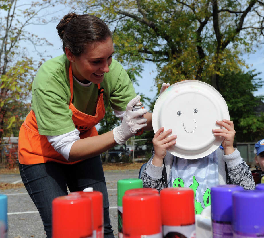 Old Greenwich School teacher, Tiffany Vaccari, left, uses an aerosol spray to color the hair of Axel Hamilton, 5, of Greenwich, who is using a smiley paper plate to cover his face during the process at the Old Greenwich School Pumpkin Patch event, Old Greenwich, Saturday, Oct. 19, 2013. Photo: Bob Luckey / Greenwich Time