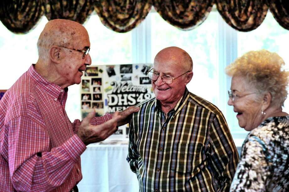 Don Edwards, left, who travelled from Arizona, talks with Bill and Germaine Lucas, who travelled from California, for the Danbury High School class of 1948's  65th reunion Saturday, Oct. 19, 2013, at Anthony's Lake Club, in Danbury, Conn. Photo: Michael Duffy / The News-Times