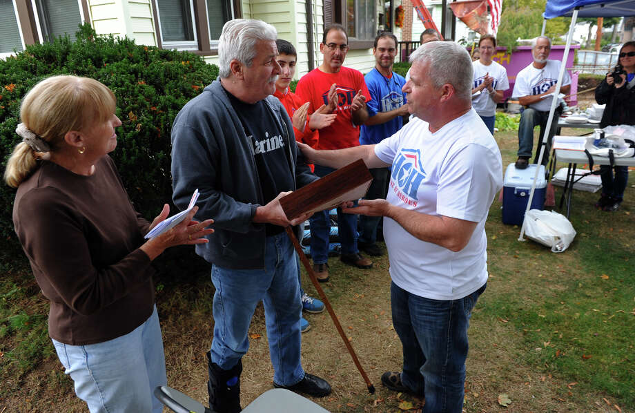 Volunteers look on as Bill May, Chairman of the Connecticut Chapter of House of Heroes, at right, presents a flag that was flown above the US Capitol to veteran Floyd MacDaniel, during a short ceremony to honor his service at his home in Stratford, Conn. on Saturday October 19, 2013. At left is Floyd's wife Elizabeth. House of Heroes volunteers perform much-needed repairs to the homes of military veterans. Photo: Christian Abraham / Connecticut Post