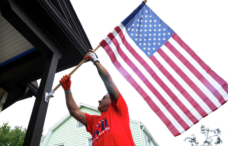 Steve Cavenaugh, a volunteer with the Connecticut Chapter of House of Heroes, puts a new flag into place at the home of veteran Floyd MacDaniel, in Stratford, Conn. on Saturday October 19, 2013. House of Heroes volunteers perform much-needed repairs to the homes of military veterans. Photo: Christian Abraham / Connecticut Post