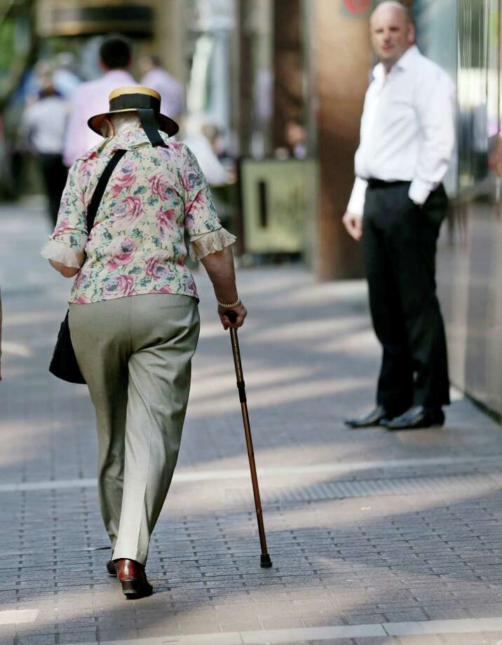 ADVANCE FOR USE SUNDAY, OCT. 20, 2013 AND THEREAFTER - In this Friday, Oct. 11, 2013 photo. an elderly woman uses a cane to walk in Sydney. Only one in five older people worldwide has a pension, according to the World Health Organization. (AP Photo/Rick Rycroft) ORG XMIT: NY796 Photo: Rick Rycroft / AP