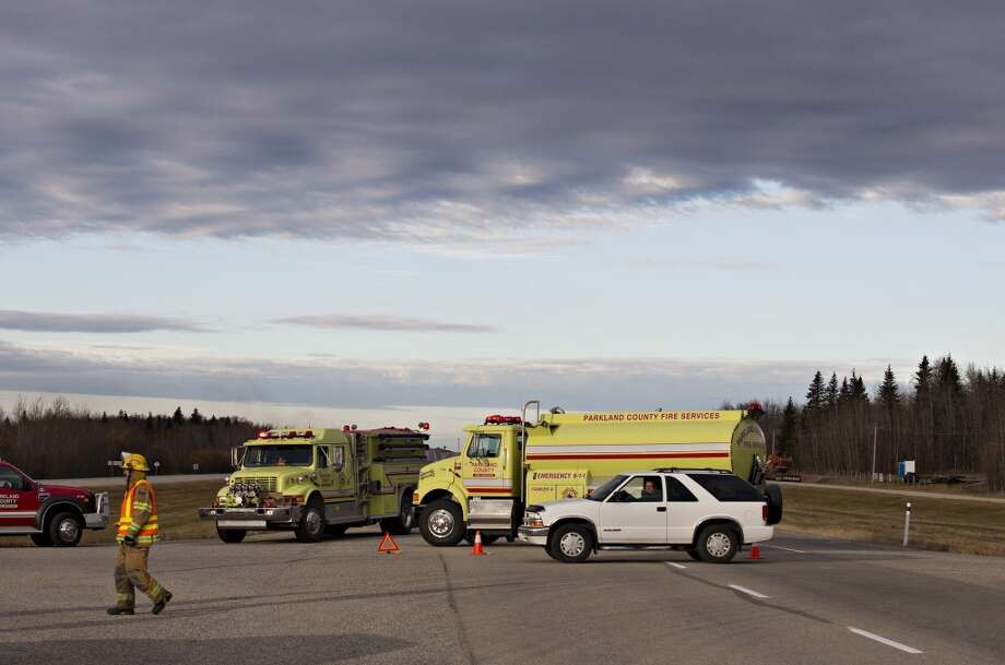 Firefighters block the highway near Gainford, Alberta, Canada as emergency crews battle a massive fire after a CN tanker train carrying oil and gas derailed in Gainford, west of Edmonton on Saturday, Oct. 19, 2013.  Canadian National spokesman Louis-Antoine Paquin said 13 cars, four carrying petroleum crude oil and nine loaded with liquified petroleum gas, came off the tracks around 1 a.m. local time in the hamlet of Gainford, about 50 miles from Edmonton. The entire community of roughly 100 people was evacuated. Photo: JASON FRANSON, AP