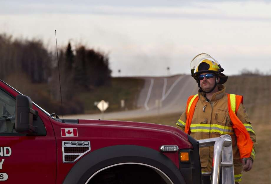 Firefighters block the highway near Gainford, Alberta, Canada as emergency crews battle a massive fire after a CN tanker train carrying oil and gas derailed in Gainford,west of Edmonton on Saturday, Oct. 19, 2013.  Canadian National spokesman Louis-Antoine Paquin said 13 cars, four carrying petroleum crude oil and nine loaded with liquified petroleum gas, came off the tracks around 1 a.m. local time in the hamlet of Gainford, about 50 miles (80 kilometers) from Edmonton. The entire community of roughly 100 people was evacuated. Photo: Jason Franson, AP