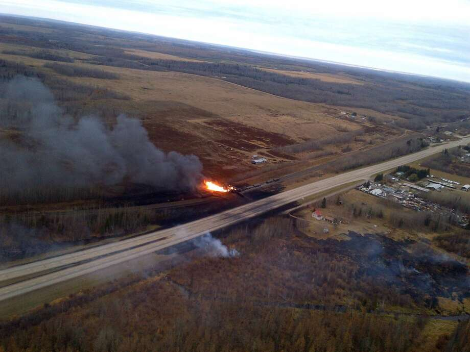Emergency crews work a massive fire after a CN tanker train carrying oil and gas derailed in Gainford, Alberta, Canada, west of Edmonton on Saturday, Oct. 19, 2013.  Canadian National spokesman Louis-Antoine Paquin said 13 cars, four carrying petroleum crude oil and nine loaded with liquified petroleum gas, came off the tracks around 1 a.m. local time in the hamlet of Gainford, about 50 miles (80 kilometers) from Edmonton. The entire community of roughly 100 people was evacuated. Photo: Royal Canadian Mounted Police, AP