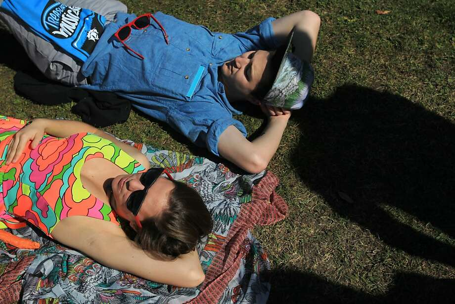 Hannah Cardenas, 22, left, and J.T. Albright, 23, lounge on the ground while listening to Giraffage during the Treasure Island Music Festival October 19, 2013 on Treasure Island in San Francisco, Calif. Photo: Leah Millis, The Chronicle