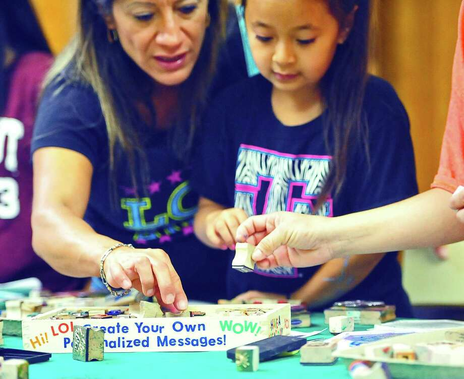 Asia Tran, 8, of Bridge City, works on embellishing her book with help from her mom, Yvette Canales, Saturday at Illustrated Family Day, hosted by the Stark Museum of Art. Photo: Sarah Moore