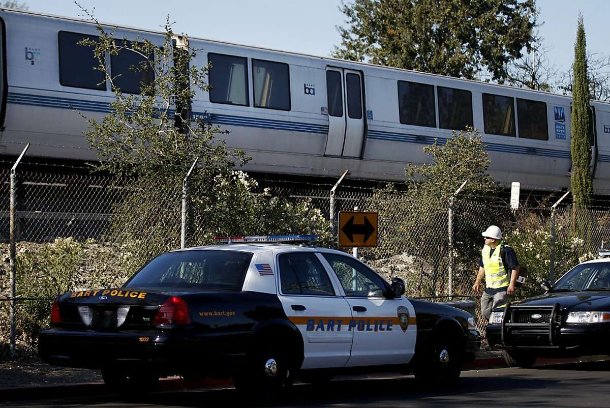 A BART worker walks past a stopped train as police investigate an accident scene where a BART train struck two people, neither of which survived, October 19, 2013 in Walnut Creek, Calif.