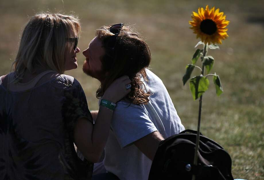 Angus Funkhouser, 28, right, goes in for a kiss with his girlfriend Morgan Jones, 26, as they lounge between stages with friends during their fourth Treasure Island Music Festival October 19, 2013 on Treasure Island in San Francisco, Calif. Photo: Leah Millis, The Chronicle