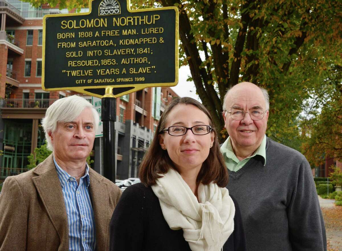 Local authors, from left, David Fiske, Rachel Seligman, and Clifford Brown pose at the Solomon Northup historical marker Wednesday Oct. 16, 2013, on Broadway in Saratoga Springs, NY. They have written a new, full biography of Solomon Northup. (John Carl D'Annibale / Times Union)