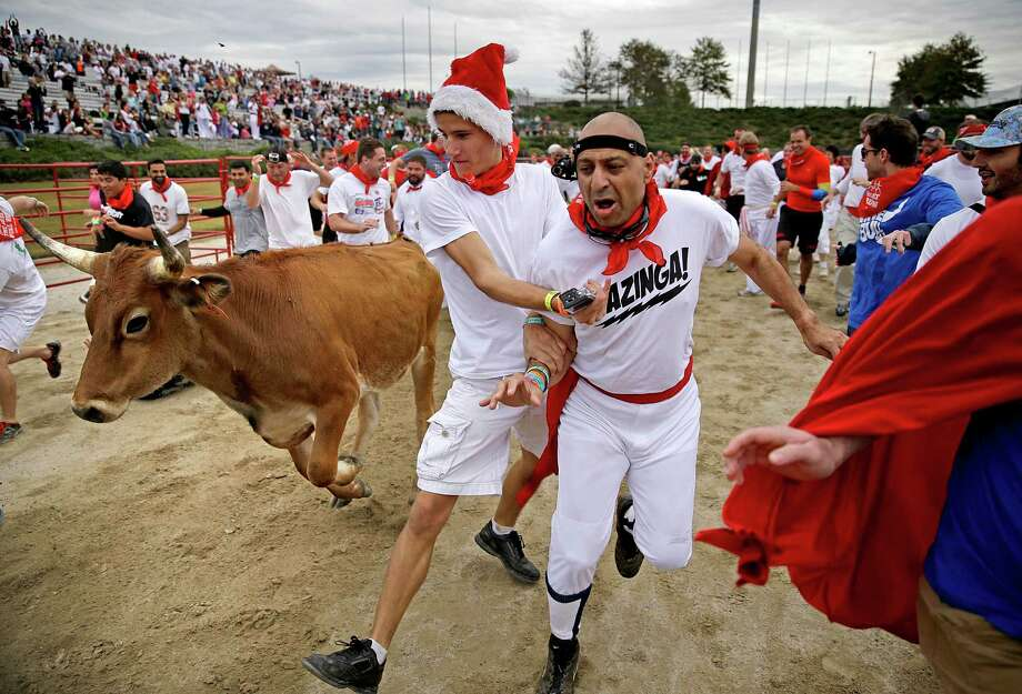 Participants run alongside charging bulls during the Great Bull Run at the Georgia International Horse Park, Saturday, Oct. 19, 2013, in Conyers, Ga. The event, expected to attract 3,000 runners Saturday, is inspired by the annual running of the bulls in Pamplona, Spain and has future stops planned in Texas, Florida, California, Illinois and Pennsylvania. Photo: David Goldman, Associated Press / AP