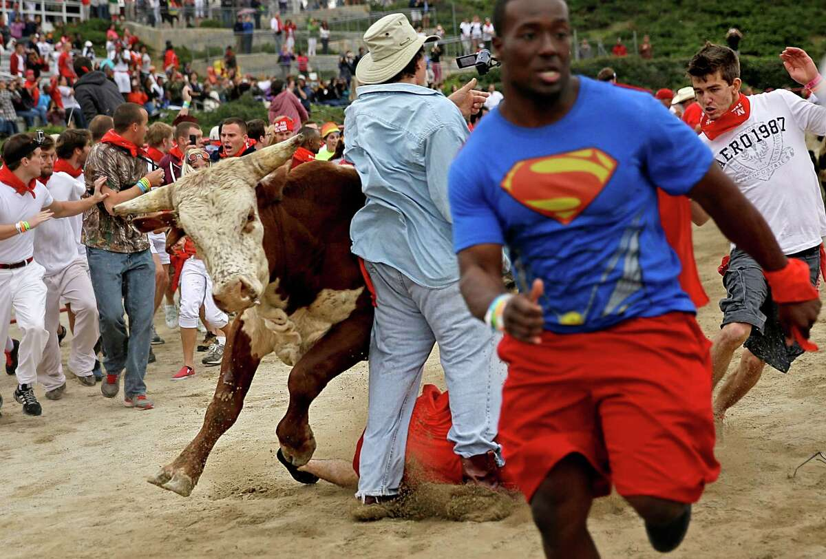 Participants are knocked over by charging bulls during the Great Bull Run at the Georgia International Horse Park, Saturday, Oct. 19, 2013, in Conyers, Ga.