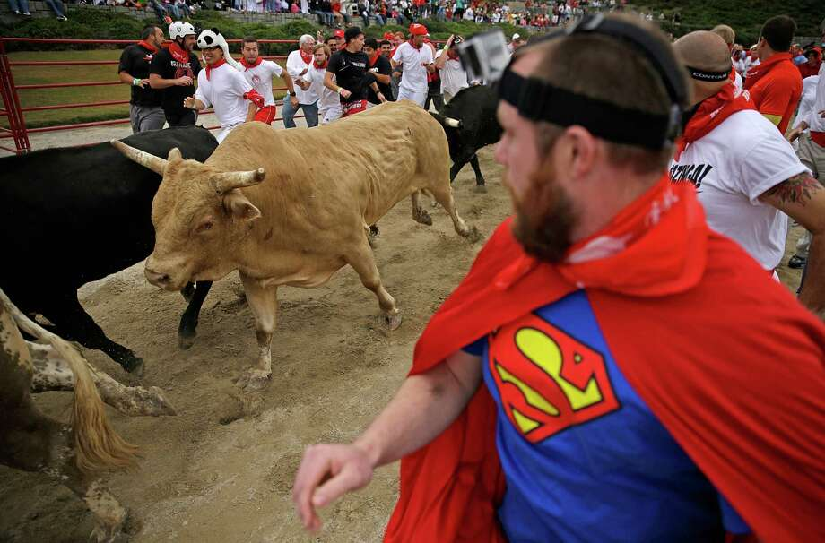 Participants run alongside charging bulls during the Great Bull Run at the Georgia International Horse Park, Saturday, Oct. 19, 2013, in Conyers, Ga. Photo: David Goldman, Associated Press / AP