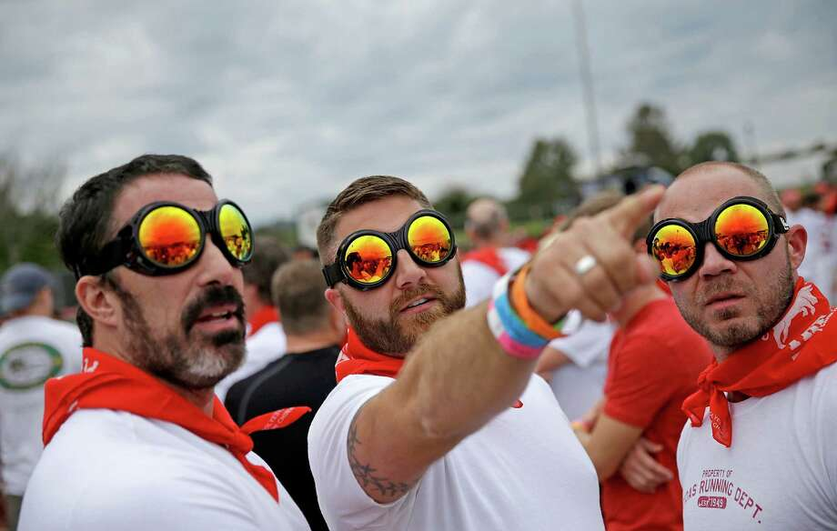 Eddy Fernandez, left, Mike Woodside, center, both of Atlanta, and Michael Kelley, of Knoxville, Tenn., wear goggles before running alongside charging bulls during the Great Bull Run at the Georgia International Horse Park, Saturday, Oct. 19, 2013, in Conyers, Ga. Photo: David Goldman, Associated Press / AP