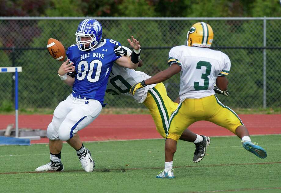 Jack Garfield of Darien lets go of the ball after scoring a touchdown during Saturday's football game against Trinity Catholic at Darien High School on October 19, 2013. Photo: Lindsay Perry / Stamford Advocate