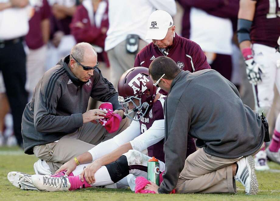 Texas A&M quarterback Johnny Manziel (2) is looked at by the training staff after suffering an injury in the fourth quarter if an NCAA college football game against Auburn Saturday, Oct. 19, 2013, in College Station, Texas. Auburn won 45-41. (AP Photo/Bob Levey) Photo: BOB LEVEY, Associated Press / FR156786 AP