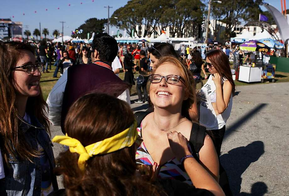 Sarah Burnand watches Kathryn Dari pour gold glitter on Marissa Morin at the Treasure Island Music Festival in San Francisco, Calif. on Saturday, Oct. 19, 2013. Photo: Raphael Kluzniok, The Chronicle