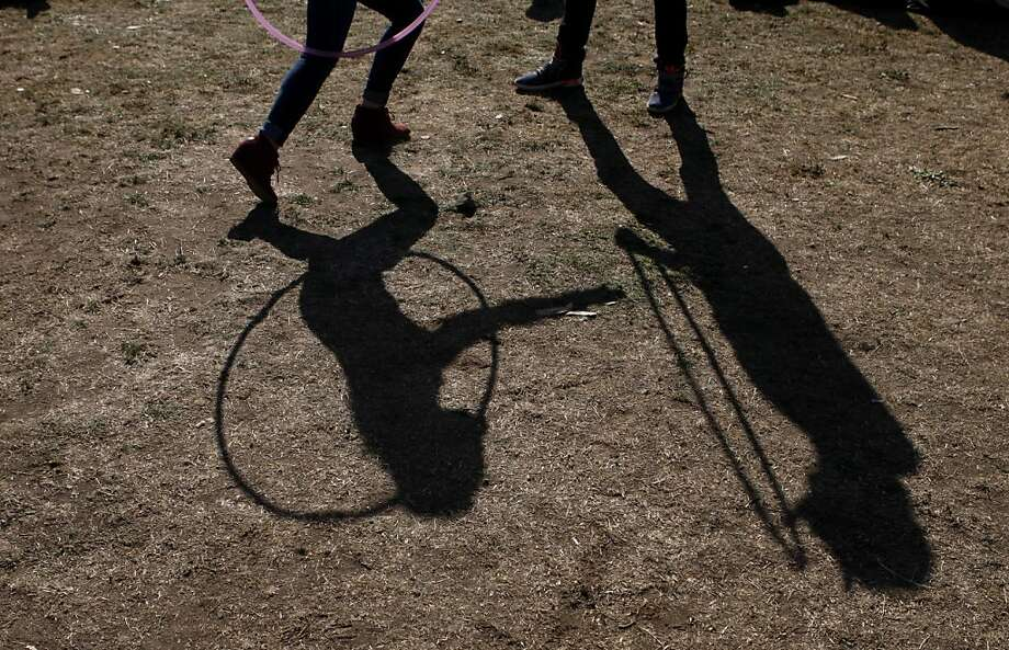Sonia Kedzierski's (left) shadow is seen while she and another festival goer dance with hoops at the Treasure Island Music Festival in San Francisco, Calif. on Saturday, Oct. 19, 2013. Photo: Raphael Kluzniok, The Chronicle