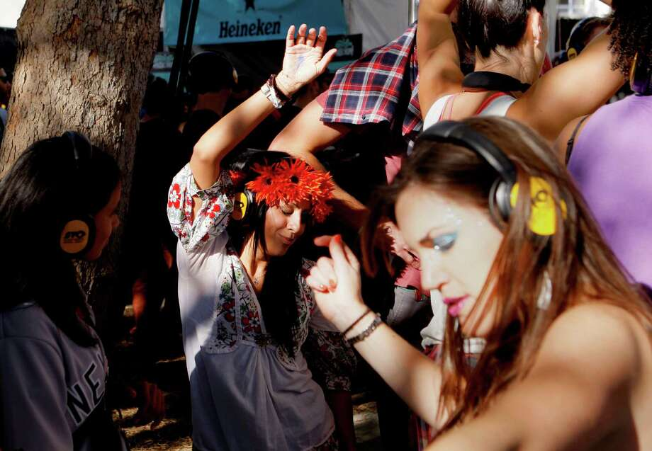 Danie Hernandez of Chicago (center) dances at the Silent Frisco area where the crowd listens to a DJ through wireless headphones at the Treasure Island Music Festival in San Francisco, Calif. on Saturday, Oct. 19, 2013. Photo: Raphael Kluzniok / The Chronicle / ONLINE_YES