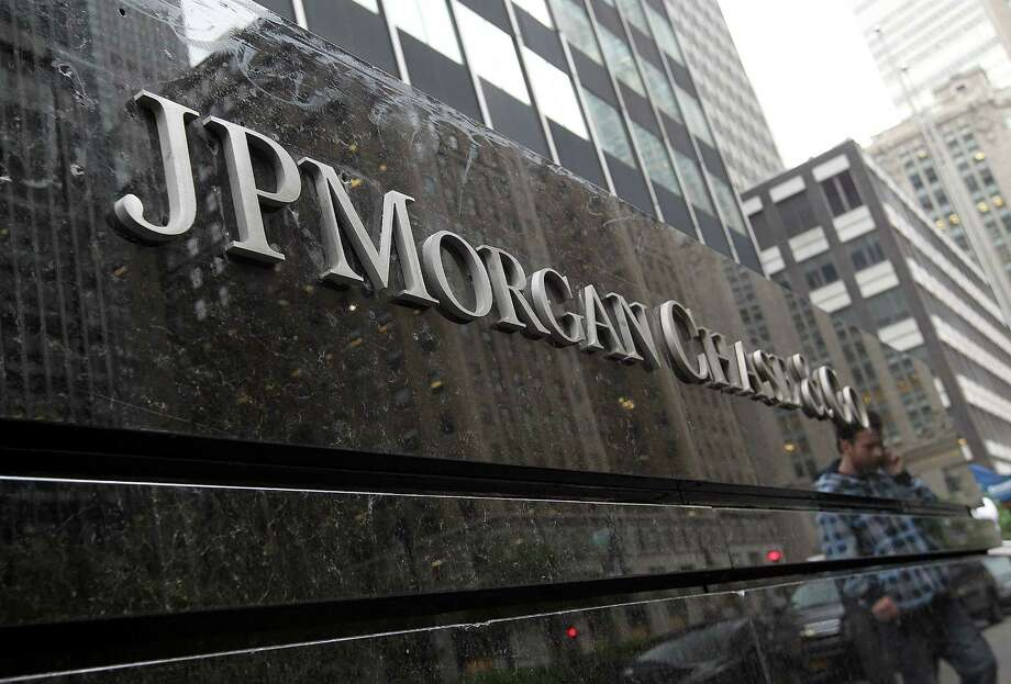 FILE - OCTOBER 11:  According to reports on October 11, 2013, JPMorgan Chase has reported a net loss in the third-quarter of $380 million.  NEW YORK, NY - MAY 14:  A man is reflected in a sign outside of the JPMorgan Chase headquarters on May 14, 2012 in New York City.  Following a $2 billion trading blunder, JPMorgan Chase's chief investment officer Ina Drew retired and will be succeeded by Matt Zames, an executive from JPMorgan's investment bank. At least two others are also being held accountable for the mistake.  (Photo by Justin Sullivan/Getty Images) ORG XMIT: 144575125 Photo: Justin Sullivan / 2012 Getty Images