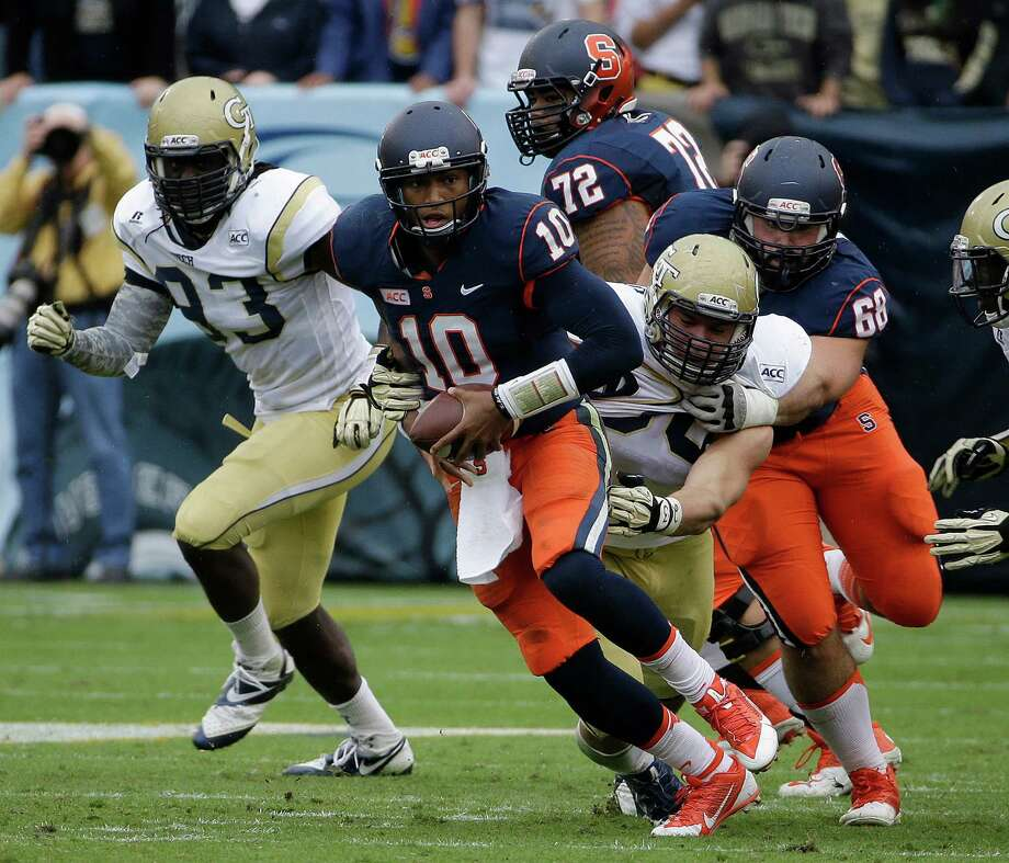 Syracuse quarterback Terrel Hunt (10) runs as Syracuse guard Nick Robinson (68) blocks Georgia Tech defensive end Anthony Williams (56) in the first half of an NCAA college football game  Saturday, Oct. 19, 2013, in Atlanta. (AP Photo/John Bazemore) ORG XMIT: GAJB107 Photo: John Bazemore / AP