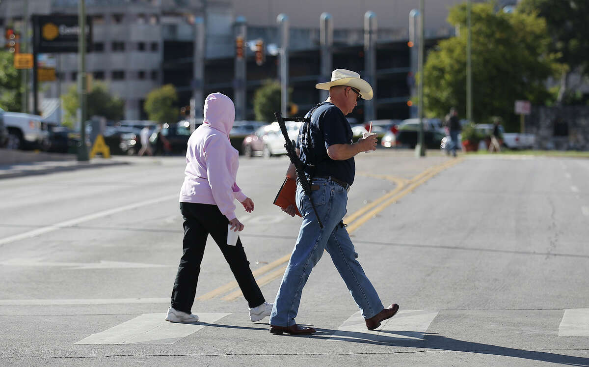 A gun owner walks across Third Street on his way to the Alamo to take part in the Come And Take It San Antonio pro-gun rally on Saturday, Oct. 19, 2013. Several hundred pro-gun owners displayed their rifles and long arms at a rally on the grounds of the Alamo. The group later marched to Travis Park where the event concluded.