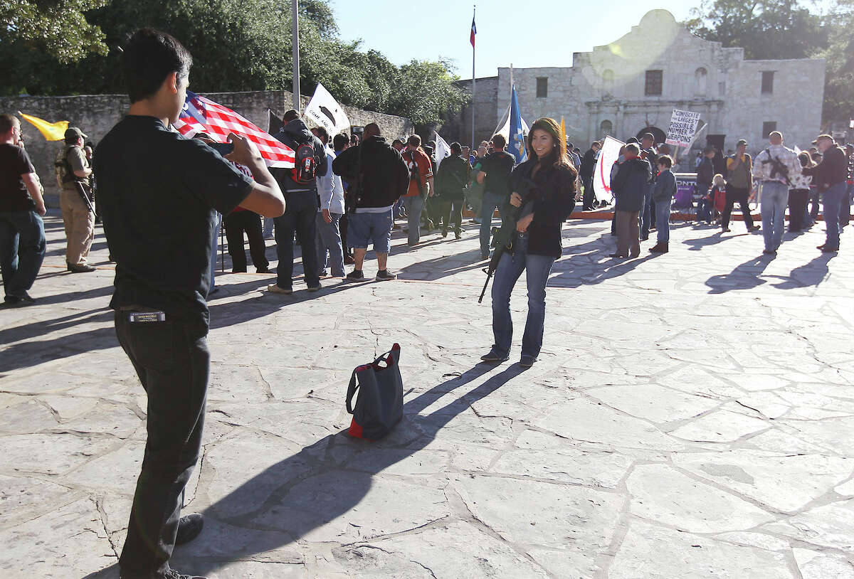 Jason Laa (left) takes a picture of Amber Rogers in front of the Alamo before the start of the Come And Take It San Antonio pro-gun rally on Saturday, Oct. 19, 2013.