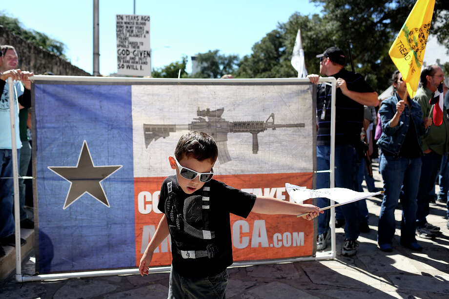 "Devin Mott, 6, of Austin, waves a flag as the crowd at ""Come and Take It"" rally gathers to move from the Alamo to Travis Park on Saturday, Oct. 19, 2013. Photo: Lisa Krantz, SAN ANTONIO EXPRESS-NEWS / SAN ANTONIO EXPRESS-NEWS"