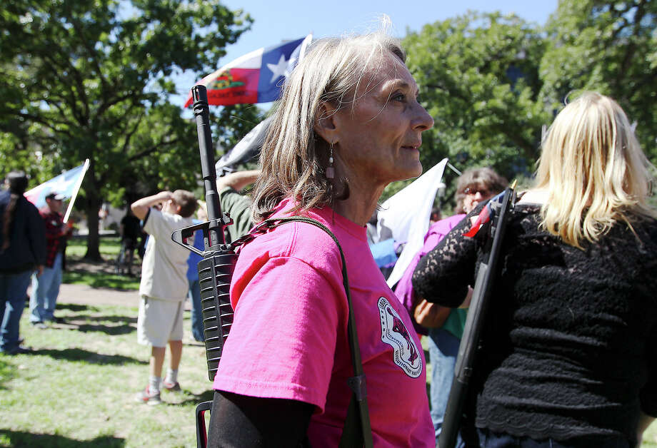 Tonya Benson carries her AR-15 rifle after marching to Travis Park as part of the Come And Take It San Antonio pro-gun rally on Saturday, Oct. 19, 2013. Photo: Kin Man Hui, San Antonio Express-News / ©2013 San Antonio Express-News