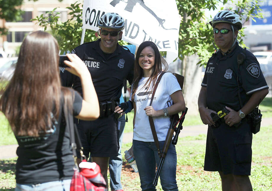 Ashley Carlisle (center) shoulder her .30-30 rifle as she gets a photo taken with San Antonio Police officers at Travis Park during the Come And Take It San Antonio pro-gun rally on Saturday, Oct. 19, 2013. Photo: Kin Man Hui, San Antonio Express-News / ©2013 San Antonio Express-News
