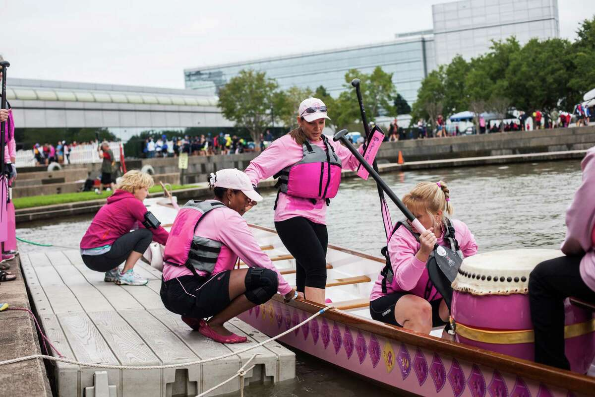 Betsy Walker of Dickinson, TX climbs into the boat before her team's race at the Houston Dragon Boat Regatta Saturday Oct. 19, 2013 in Sugar Land. Her team, Pink Phurree, is a dragon boat racing team compiled entirely of breast cancer survivors.
