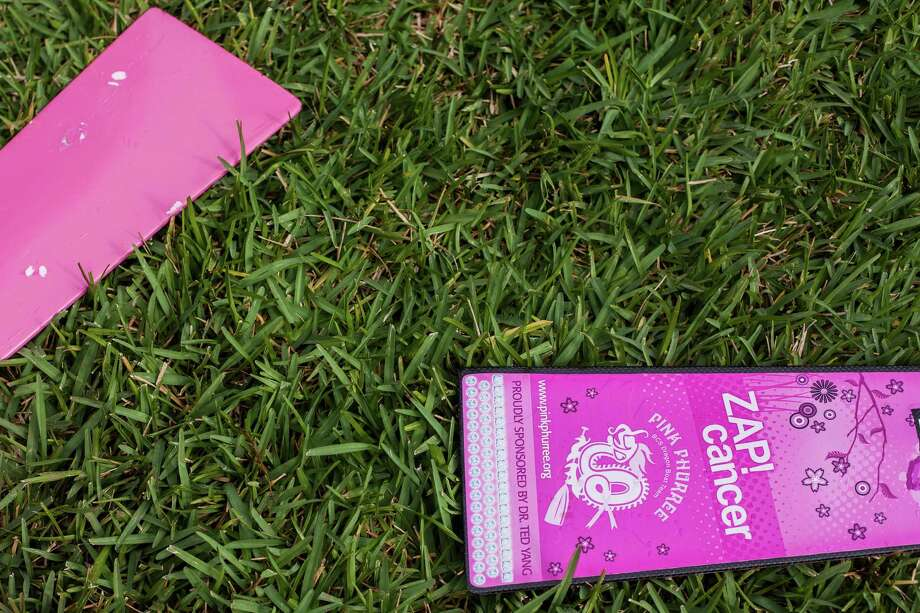Team Pink Phurree's paddles lay in the grass shortly after a race at the Houston Dragon Boat Regatta Saturday Oct. 19, 2013 in Sugar Land. Pink Phurree is a dragon boat racing team compiled entirely of breast cancer survivors. Photo: Michael Starghill, Jr., For The Chronicle / © 2013 Michael Starghill, Jr.