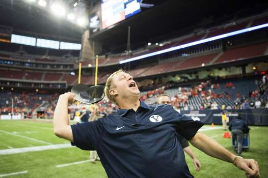 Brigham Young head coach Bronco Mendenhall tosses his hat into the stands as he celebrates the victory. Photo: Smiley N. Pool, Houston Chronicle