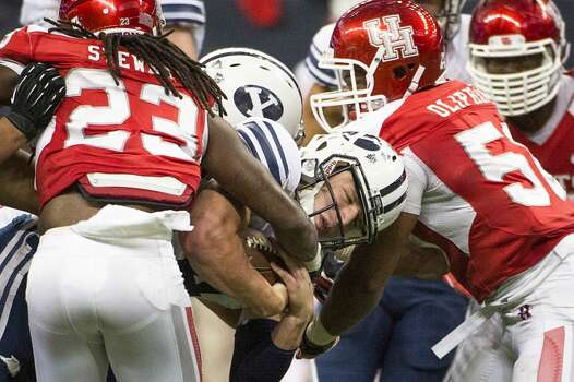 Brigham Young quarterback Taysom Hill is brought down by Houston defensive back Trevon Stewart (23) and linebacker Efrem Oliphant. Photo: Smiley N. Pool, Houston Chronicle