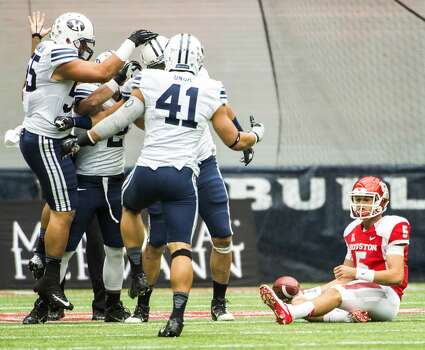 Houston quarterback John O'Korn (5) sits on the turf as the Brigham Young defense celebrates a sack. Photo: Smiley N. Pool, Houston Chronicle
