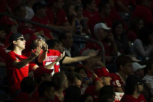 A pair of Houston fans basks in a ray of sunlight streaming into their section. Photo: Smiley N. Pool, Houston Chronicle