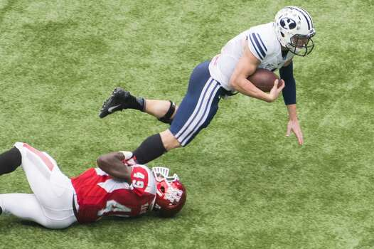 Brigham Young quarterback Taysom Hill is tripped up by Houston linebacker Derrick Mathews. Photo: Smiley N. Pool, Houston Chronicle