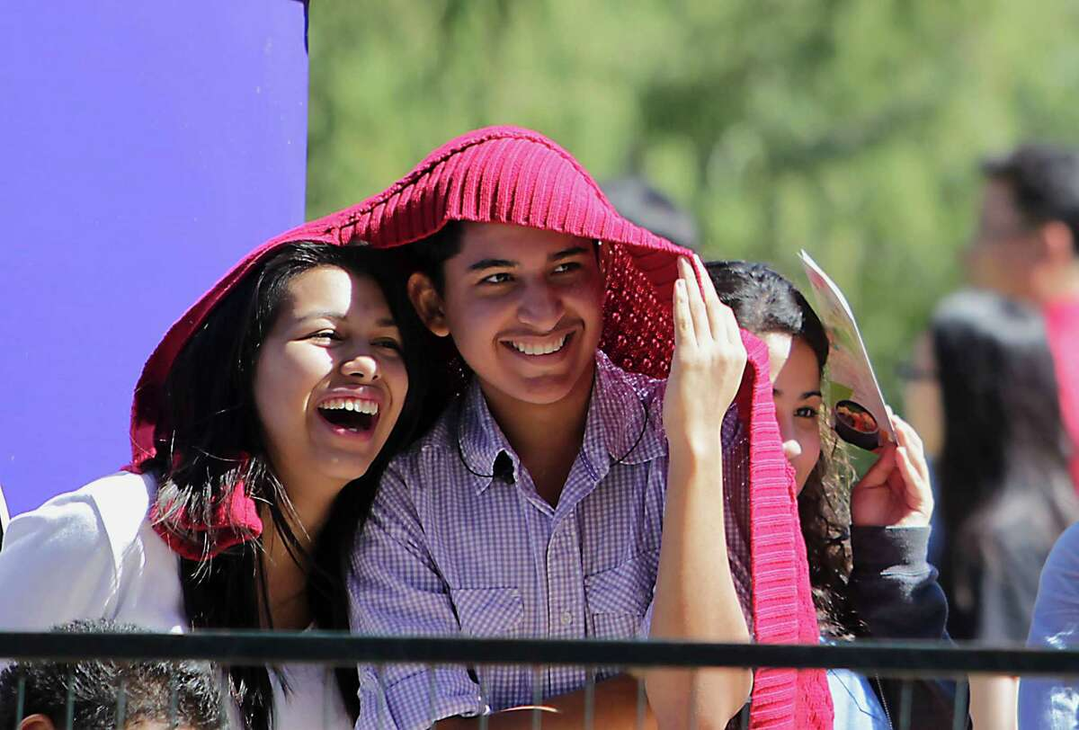Estephanie Zapata, left, and Jesus Rojas watch a performance during the Korean Festival at Discovery Green Saturday, Oct. 19, 2013, in Houston.