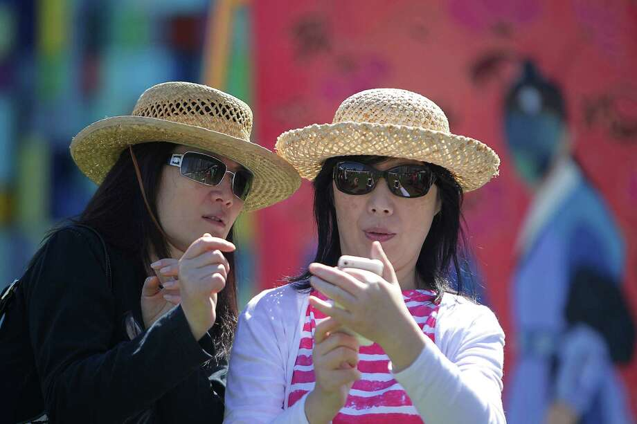 Jenny Combast, left, and her sister Wang Qi during the Korean Festival at Discovery Green Saturday, Oct. 19, 2013, in Houston. Photo: James Nielsen, Houston Chronicle / © 2013  Houston Chronicle